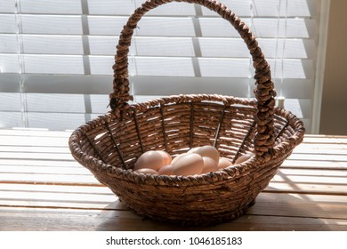 Fresh brown eggs in a wicker basket placed on wooden table with window sunlight natural pecan wood planks