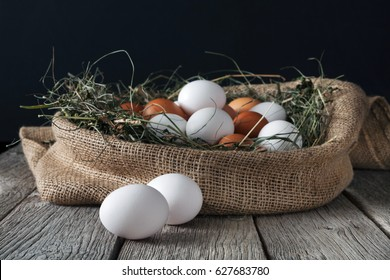 Fresh brown and white eggs in burlap sack at rustic wood isolated on black background