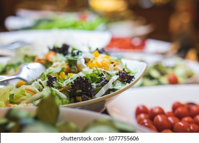A fresh buffet of a colorful variety of healthy organic salads. Focus is on a salad bowl of mixed leafs and carrots, and there is a bowl of tomatoes on the right side.