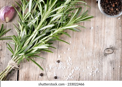 Fresh bunch of rosemary, garlic, pepper and salt on wooden table. Aromatic evergreen herb, many culinary - roasted meats. Copyspace.