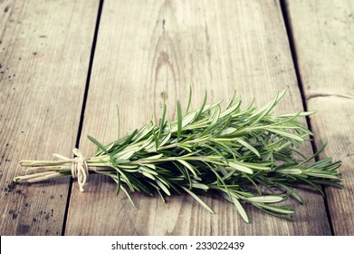 Fresh bunch of rosemary on wooden table. Aromatic evergreen herb, many culinary and medicinal uses. Copyspace.