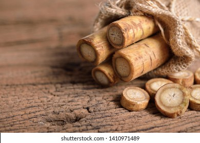 fresh burdock root or Gobo in sack and on wooden background