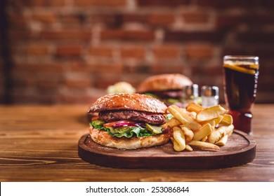 Fresh burger closeup on wooden table.