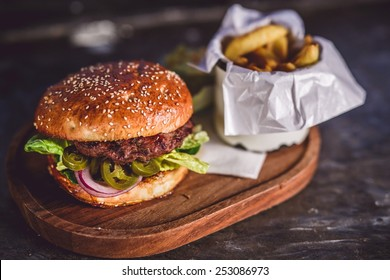 Fresh burger closeup on wooden table.