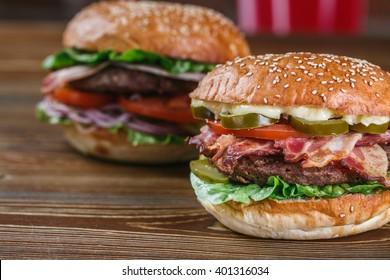 Fresh burger closeup. Sesame bun, beef, bacon, lettuce, pepper. Secon burger in the background.