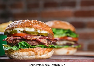 Fresh burger closeup. Sesame bun, beef, bacon, lettuce, pepper.