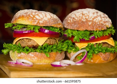 Fresh burger, decorated vegetables and grilled cutlet. Dark background. Home cooking. Fastfood unhealthy concept. Tradition gourmet snack. High calorie food. American table.