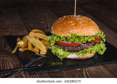 Fresh burger and french fries closeup on wooden table.