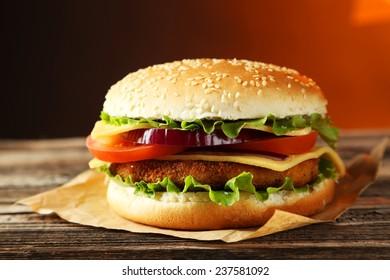 Fresh burger on brown wooden background