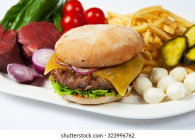 Fresh burger in plate with vegetables and french fries. Big hamburger with fries and salad.