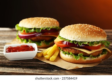 Fresh burgers on brown wooden background