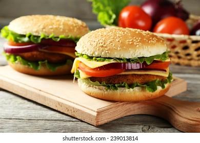 Fresh burgers on cutting borad on grey wooden background
