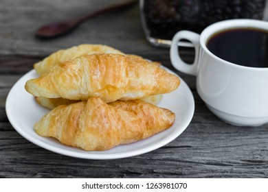 Fresh butter croissants with coffee on old wooden table