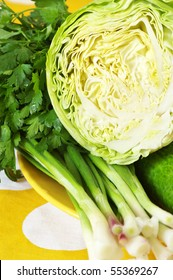 Fresh cabbage, cucumbers, spring onion and parsley in yellow plate on yellow/white cloth.