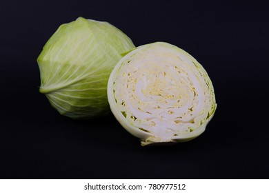 Fresh cabbage on black background. Raw cabbages, vegetarian food for salad. Natural uncooked vegetable.
