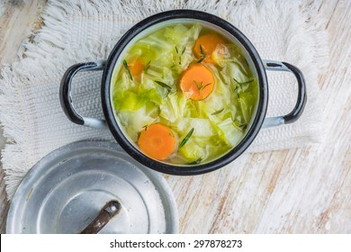 Fresh cabbage soup in a pot on white wooden table