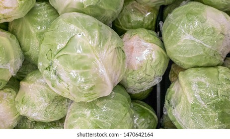 Fresh cabbage wrap in plastic shrink wrap pile in market