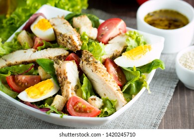 Fresh Caesar salad made of tomato, ruccola, chicken breast, eggs, arugula, crackers and spices. Organic ingredients in a white, transparent bowl on wooden background