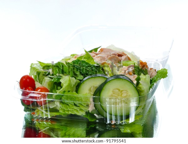Fresh Caesar salad in a take out container with reflection