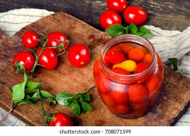 Fresh and canned tomatoes on rustic wooden table
