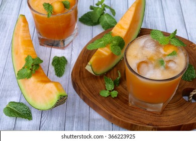 Fresh cantaloupe juice with foam still present. Served in a small tumbler with ice cubes; garnished with mint leaves. Arranged on a wooden board, decorated with cantaloupe wedges.