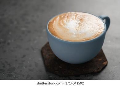 Cappuccino frais en tasse bleue sur fond concret