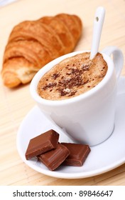 Fresh cappuccino with few pieces of chocolate for breakfast