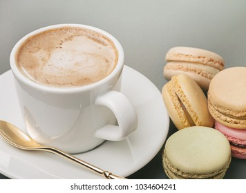 Fresh cappuccino in white cup, spoon on  saucer and colorful french macaroons. Copy space.