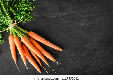 Fresh carrot bunch on dark stone table or black background top view, copy space.