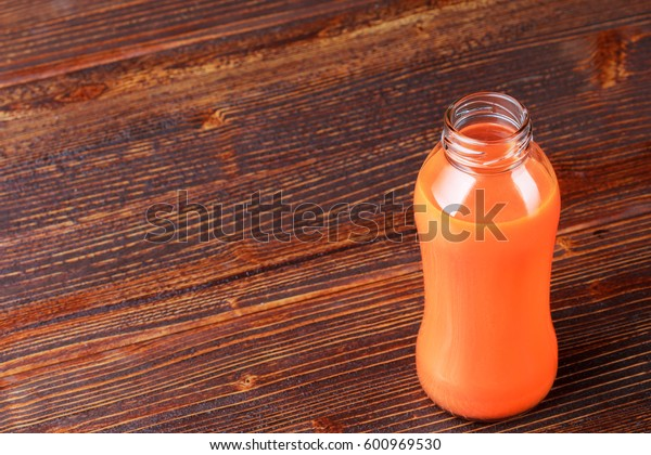 Fresh carrot juice in bottle on an old brown wooden table