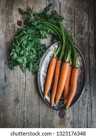 Fresh carrot with leaves on silver tray and wooden background. Overlay shot.