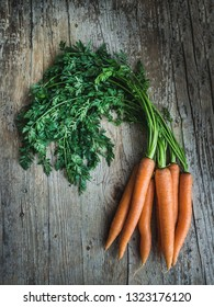 Fresh carrot with leaves on wooden background. Overlay shot.