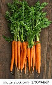 Frische Karotten mit grünen Blättern auf rustikalem Holzhintergrund