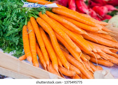 Fresh carrots are laid out on a counter of the market