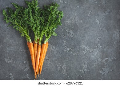 Fresh carrots. Carrots on black background. Flat lay, top view, copy space