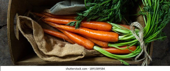 Fresh carrots on rustic kitchen with canvas bag in rustic wooden box. Flat lay, top view. Fresh organic vegetables carrots, freshly picked carrots with leaves