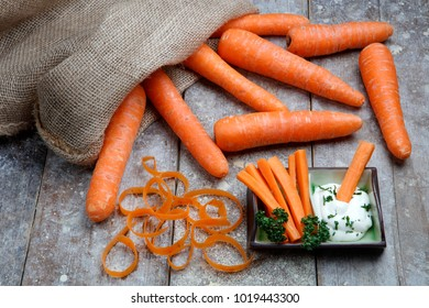 Fresh carrots spilling from a sack on old wooden table with carrot sticks and parsley dip