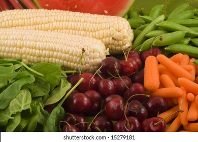Fresh carrots,sugar snap peas, white corn,rhubarb, watermelon, baby spinach and cherries make up this healthy grouping of fruits and vegetables.
