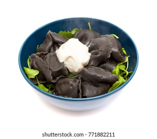 fresh cattlefish ink Tortellini stuffed pasta isolated with rocket  salad leaves and a blob of sour cream