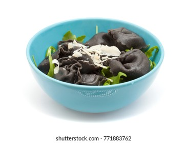 fresh cattlefish ink Tortellini stuffed pasta isolated with rocket  salad leaves and fres parmesan shavings on white background