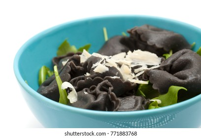 fresh cattlefish ink Tortellini stuffed pasta isolated with rocket  salad leaves and fresh parmesan shavings on white background