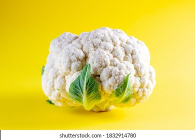 Fresh cauliflower on yellow background. Seasonal vegetables minimal style. Food in minimal style.