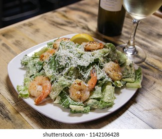 Fresh ceasar salad with shrimp.  Accompanied by a bottle of wine and a glass of wine.