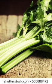 Fresh celery stalks, vintage wooden background, selective focus