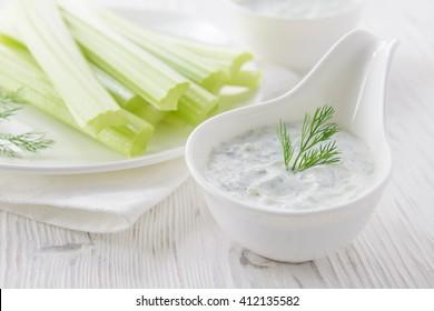 Fresh celery sticks with yogurt dip on white wooden background, selective focus