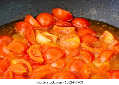 Fresh cerry tomatoes cooking in a pan. Close up.