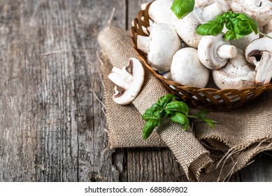 Fresh champignon mushrooms in a basket on wooden table, overhead