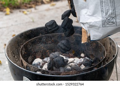 Fresh charcoal briquettes being poured on white hot coals