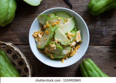 Fresh chayote fruits (Sechium edulis) stir fried with egg and garlic in bowl on wooden background