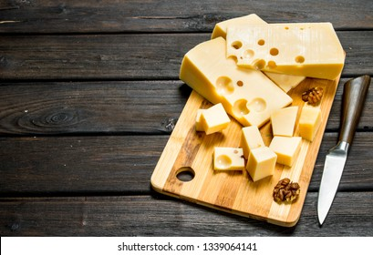 Fresh cheese with nuts on a wooden Board. On a wooden background.